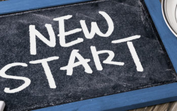 new start handwritten on blackboard
